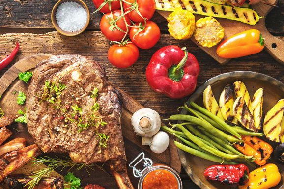 Grilled meat and vegetables on rustic wooden table - SoulSpice